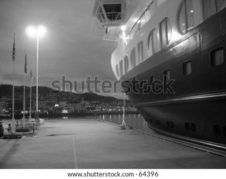 Hurtigruta cruise ship docked in black and white.