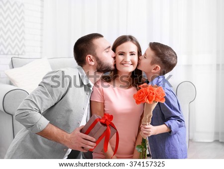 Husband and son giving gift box and roses to wife