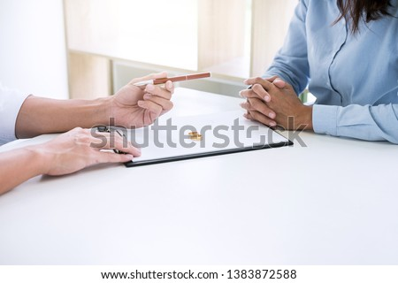 Husband and wife are reading divorce agreement and filing pen to signing decree of divorce (dissolution or cancellation) of marriage filing divorce papers and two golden marry ring. #1383872588