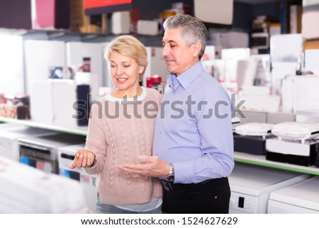 Husband and wife are visiting shop of household appliances for buying goods for kitchen and house.  #1524627629
