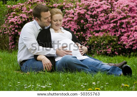 Husband and wife maternity expecting a child or baby posing in the park - stock photo