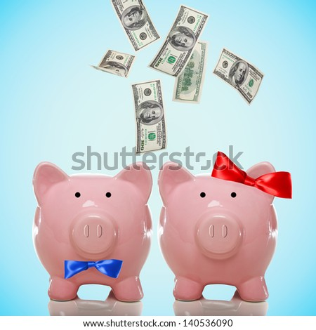 Husband and wife piggy banks with hundred dollar bills falling in or flying out