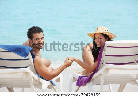 husband and wife relaxing on sunbeds on the beach and smiling at camera. Horizontal shape, rear view, copy space