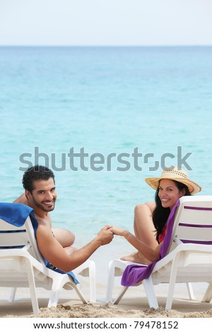 husband and wife relaxing on sunbeds on the beach and smiling at camera. Vertical shape, rear view, copy space