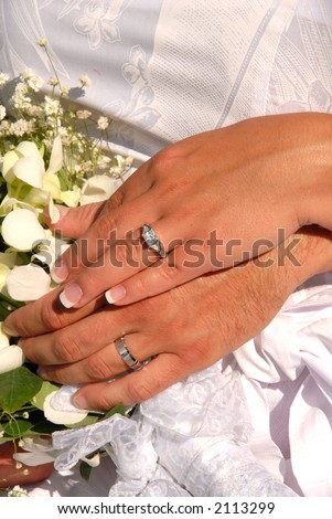 Husband and wife showing their wedding rings surrounded by the bride's bouquet.