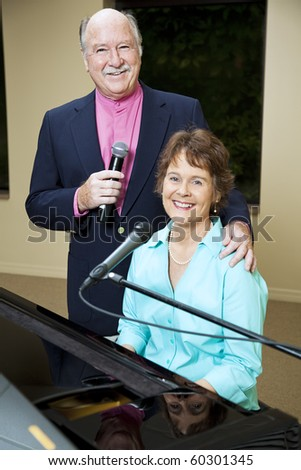 Husband and wife sing and play piano for entertainment.