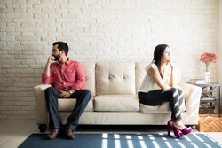Husband and wife sitting on the couch and not talking after an argument at home. Social Distancing concept