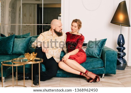 Husband and wife sitting on the couch in a spacious bright room Enjoying every minute together. Beautiful young loving couple sitting together on the couch #1368962450