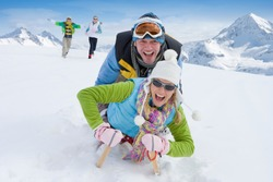 Husband and wife together sledding down a steep snowy slope on a single sled with their running in the background to chase them