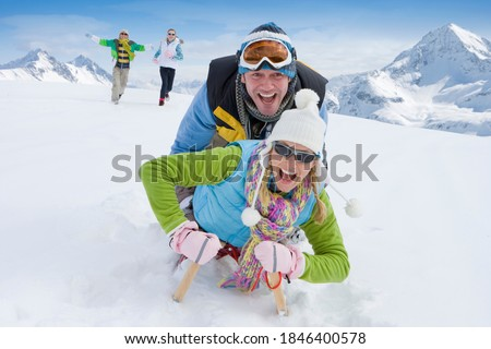 Husband and wife together sledding down a steep snowy slope on a single sled with their running in the background to chase them Stock photo ©
