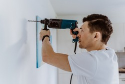 Husband for hour home repairing service. Portrait of handyman drilling a hole in wall to put the painting on.