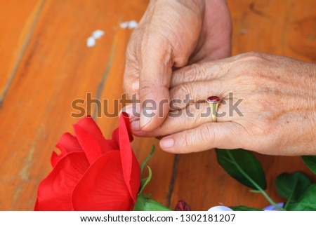 Husband giving rose flower to his wife for 30th year anniversary and holding her hand with love.Anniversary celebration,valentine's day, couple, relationships and people concept.
