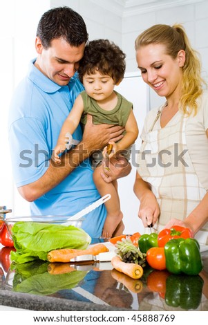 husband holding baby boy in kitchen watching wife cooking food
