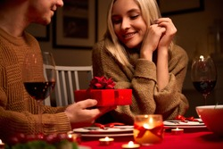 Husband holding red gift box in hands making Valentine's day present surprise to happy wife having romantic dinner date in candlelight, close up. Couple celebrate Valentine day on February 14, closeup