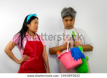 Husband holds cleaning equipment and show sadness face when his wife angry and looks with fierce eyes. #1443895832