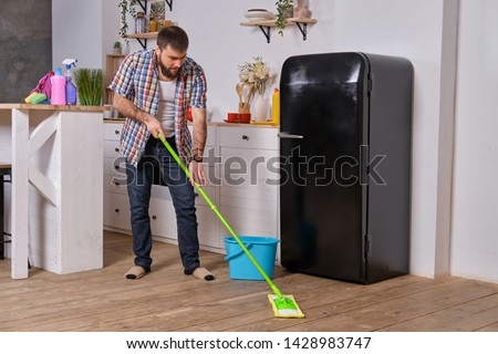 Husband housekeeper cleans the kitchen. Young happy man with green mop washes the floor #1428983747