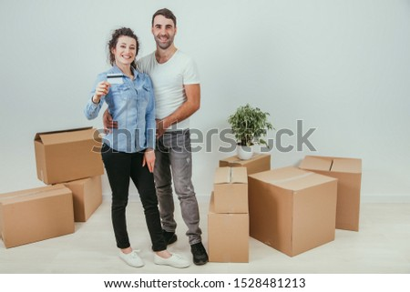 Husband is hugging his wife. Pretty wife is holding a credit card. They are smiling, surrounded by carton boxes. #1528481213