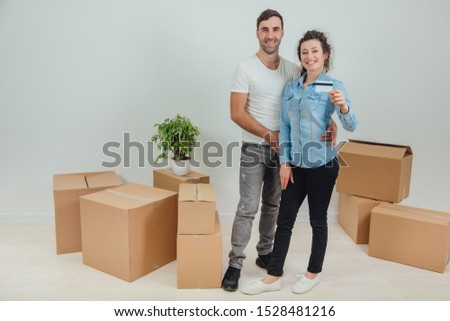 Husband is hugging his wife. Pretty wife is holding a credit card. They are smiling, surrounded by carton boxes. #1528481216