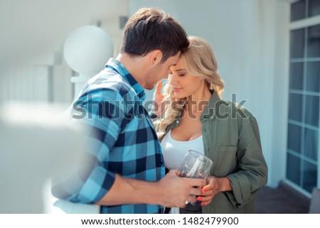Husband kissing. Husband kissing his beautiful woman while drinking coffee on balcony