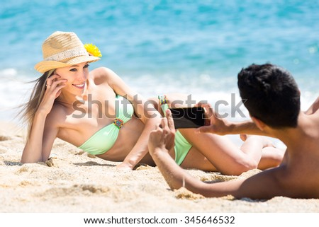 Husband photographing his sexual wife during honeymoon vacation lying on a beach sand with his smartphone #345646532