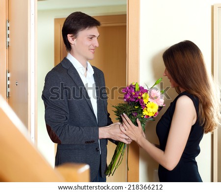 Husband present flowers to his young wife at home door