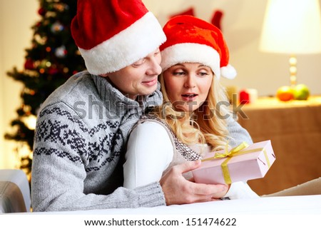 Husband surprising his beloved wife with a Christmas present
