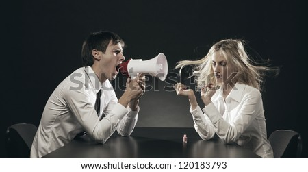 Husband using a megaphone to scream at his wife applying nail polish