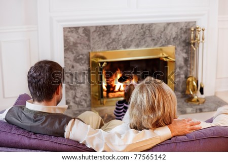 Husband & wife sit together on the sofa while their daughter reads by the fire