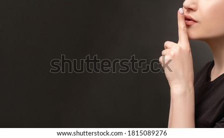 Hush gesture. Social campaign. Woman showing shhh with finger on lips isolated on black copy space ad background. Domestic violence. Family abuse. Female rights. Censorship confidential information. Photo stock ©