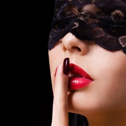 Hush. Sexy woman with finger on her red lips showing shush. Erotic girl with lace mask over black background.