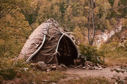 Hut of ancient people. Prehistoric dwelling place, primitive architecture. Wigwam made of animal skins surrounded with mammoth tusks. The cabin of an ancient man. Leathers shelter of primitive man