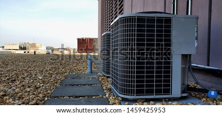 HVAC AC compressor Coil outside installation with fan and radiator and protective mech. Installed Coil on roof with rocks attached to coil lines and near concrete tiles on roof #1459425953
