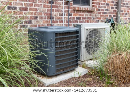 HVAC Air Conditioner Compressor and a Mini-split system together next to each other, next to a brick home.
