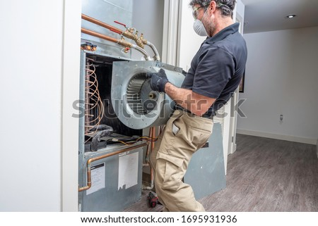 HVAC contractor wearing a mask and safety glasses repairing a motor on a heat pump
