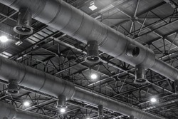 HVAC Duct Cleaning, Ventilation pipes in silver insulation material hanging from the ceiling inside new building.
