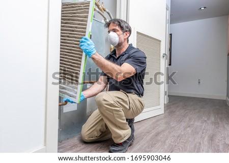 Photo of  Hvac maintenance technician removing a diry air filter from a heat pump