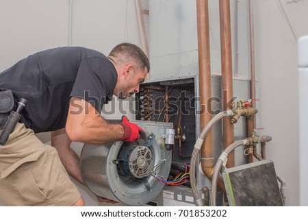Hvac repair technician removing a blower motor from air handler