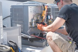 Hvac repair technician using a volt meter to test components on an air conditioner condenser.