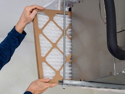 HVAC service technician changing dirty indoor air filter in residential heating and air conditioning system. Home air duct ventilation system maintenance for clean air.