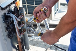 HVAC technician is working on air conditioner units on a roof of new industrial building.Technician hand using fix wrench to tighten outdoor unit of air condition. Man holds a wrench in his hand.