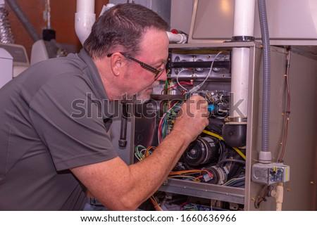 HVAC Technician Working On A High Efficiency Gas Furnace  Gray Shirt   ストックフォト ©