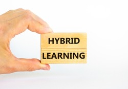 Hybrid learning symbol. Concept words 'Hybrid learning' on wooden blocks on a beautiful white background. Businessman hand. . Business, educational and hybrid learning concept, copy space.