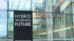 Hybrid working future sign in front of a modern office building