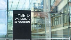 Hybrid Working Revolution sign in front of a modern office building