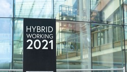Hybrid Working 2021 sign in front of a modern office building