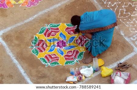 HYDERABAD,INDIA-JANUARY 7:Hindu woman drawing traditional rangoli and filling with color powders during makara sankranti festival season on January 7,2018,In Hyderabad                               #788589241