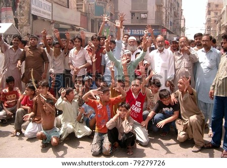 HYDERABAD, PAKISTAN - JUN 14: Residents of Lajpat road chant slogans against prolonged electricity load shedding in their area at Society Chowk on June 14, 2011 in Hyderabad.