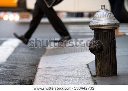 Hydrant on the street, in background walking pedestrian.