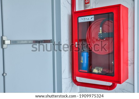 Hydrant with water hoses and fire extinguish equipment. Fire safety equipment in the red box on wall cement . Hydrant with water hoses and fire extinguish equipment  fire hose box .