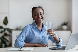 Hydration At Work. Happy Black Female Worker Holding Glass Of Mineral Water While Sitting At Workplace In White Office, Feeling Healthy And Motivated, Smiling At Camera, Copy Space